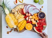 Many sliced colorful tropical fruit plate on serving tray, top view from above. Summer healthy diet, poster