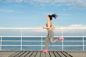 Happy Latin Fit Girl Running Alone On Bridge. Student In Tracksuit Keeping Fit And Enjoying Availabl poster
