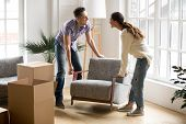 Smiling Couple Carrying Modern Chair Together Placing Furniture Moving Into New Home, Young Family D poster