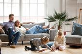 Children Sister And Brother Playing Drawing Together On Floor While Young Parents Relaxing At Home O poster