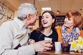 Happy Family Spending Time Together. Senoir Family Couple With Adult Daughter Chat And Laugh In Cafe poster