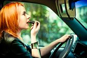 Concept Of Danger Driving. Young Woman Driver Red Haired Teenage Girl Painting Her Lips Doing Make U poster