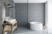 Gray Tile Bathroom Interior With A Concrete Floor, A White Bathtub, A Double Sink Standing On A Wood poster