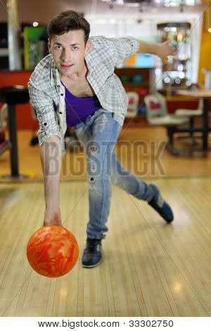 Young smiling man wearing ripped jeans throws ball in bowling; shallow depth of field