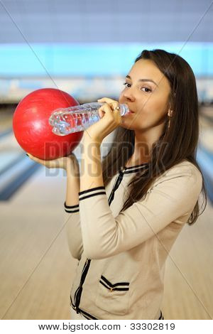 Young brunette woman holds red ball and drinks pure water from bottle in bowling club; shallow depth of field