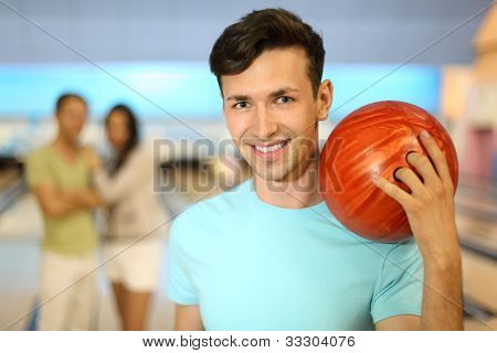 Smiling man with orange ball; couple stands behind him in bowling club; focus on right man; shallow depth of field