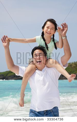 asian father with little girl running on the beach