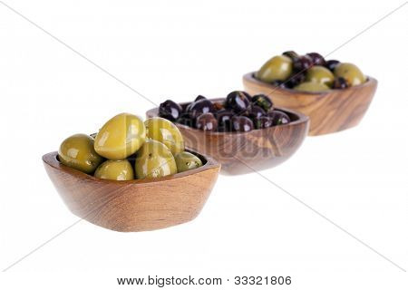 Green and black olives in white bowls over white. Intentional shallow depth of field.