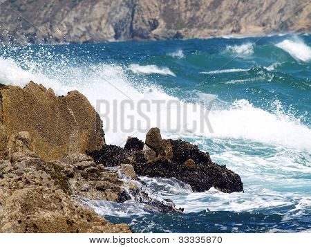 Wild Waves In Bay Against Rocky Shore Line