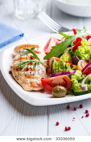Grilled chicken fillet with mediterranean salad on a plate
