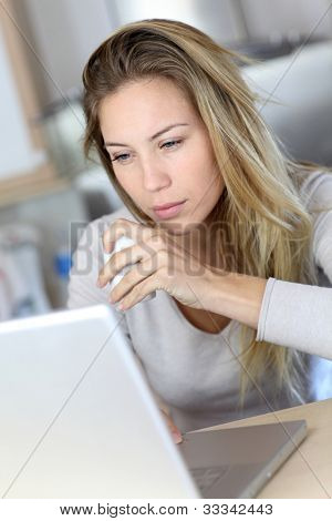 Woman checking email on laptop computer while drinking coffee