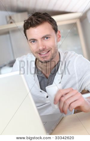 Man drinking coffee in front of laptop computer