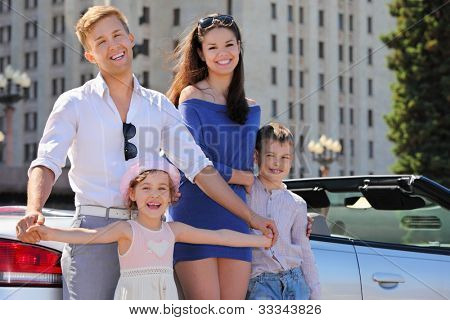 Smiling father, mother and two children stand near convertible car