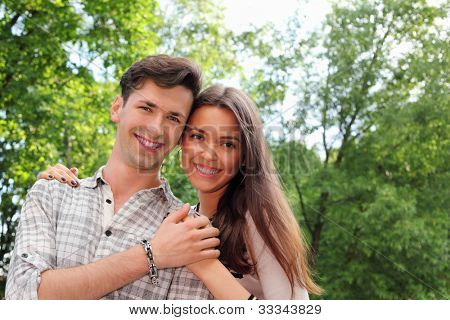 Smiling young man and woman stand in park and hold hands; green trees and sunny day