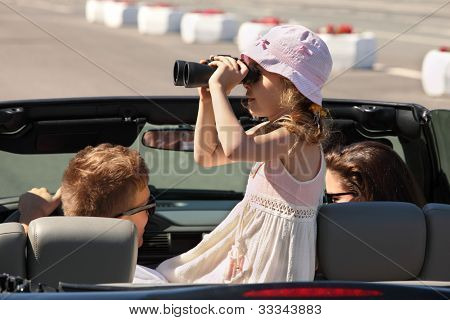 Father, mother and daughter ride in convertible car; pretty girl looks through binoculars