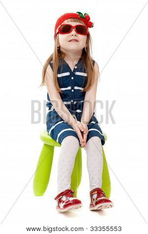 Little Girl In A Red Hat And Sunglasses Sitting On A Green Chair