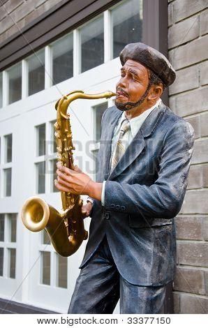 Estatua de hombre que sopla un saxofón.