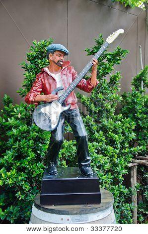 Estatua de hombre que sopla una guitarra.