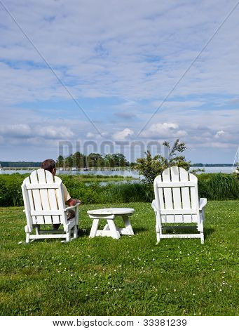 Single Senior Man In White Chairs Overlooking Bay