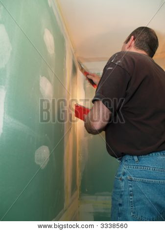 Man Spackling New Drywall