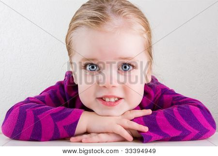 Child Resting Her Head On Her Hands Smiling