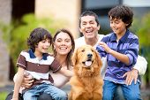 stock photo of family bonding  - Family outdoors with a dog looking very happy - JPG