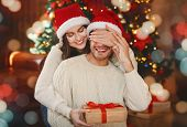 Loving Young Woman Giving Surprise Gift To Her Husband, Closing His Eyes, Celebrating Christmas At H poster