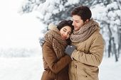 Peaceful Couple Of Lovers Embracing Standing In Snowy Winter Forest In The Morning. Winter Date Conc poster