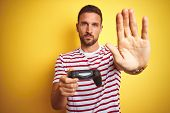Young handsome man playing video games using joystick game pad over yellow background with open hand poster