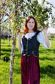 stock photo of shepherdess  - Young medieval woman standing near the birch - JPG