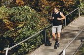Athlete Fit Man Runs Up In Slow Motion. Runner Moving On Stairs. Triathlete Workout For Triathlon. M poster