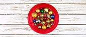 Christmas decorations design top view of Xmas balls ornaments on red plate onto horizontal white woo poster