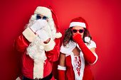 Middle age couple wearing Santa costume and sunglasses over isolated red background smelling somethi poster