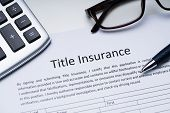 Title Insurance Form Near Calculator And Glasses poster