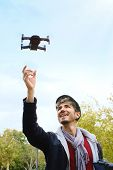 Young Man With Remote Control Landing Drone In His Hands poster