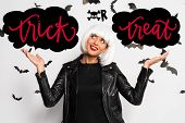 Attractive Woman In White Wig Pointing With Hands At Clouds Near Trick Or Treat Lettering poster