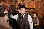 picture of chug  - Overweight man drinks from a bottle of alcohol in a saloon - JPG