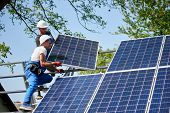 Two Workers Installing Heavy Solar Photo Voltaic Panel On Tall Steel Platform On Green Tree And Blue poster