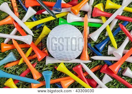 A golf ball amongst a collection of coloured wooden tees.
