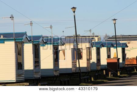 Row of caravans in trailer park at sunset.