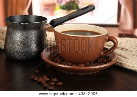 cup of coffee with scarf and coffee maker on table in room