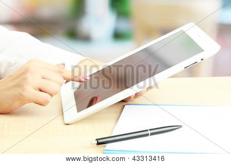 Female office worker using digital tablet in cafe