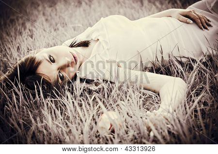Sad Beautiful Girl Lying On Grass. Faded Effect
