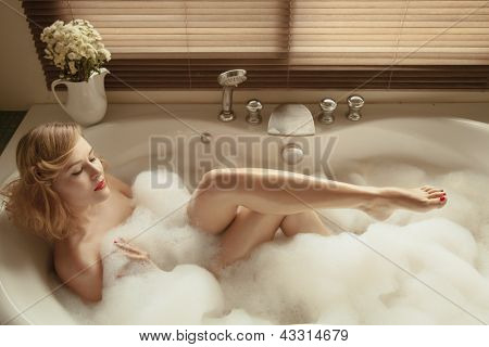Portrait of elegant beautiful woman relaxing in a spa bath