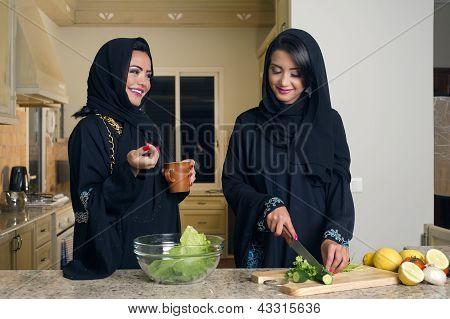 Dois encontro de mulheres árabes cozinhar & beber café na cozinha