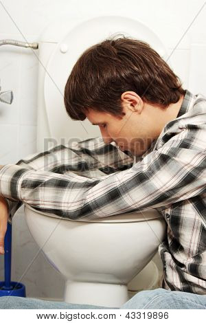 Young man (drunk or sick) vomiting