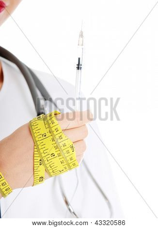Close up of female doctor hand with syringe and measuring tape, isolated on white