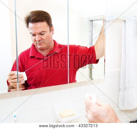 Man getting ready to floss his teeth with dental floss.