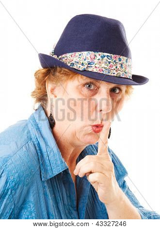 Middle-aged woman putting her finger to her lips in a hushing gesture.  Isolated on white.