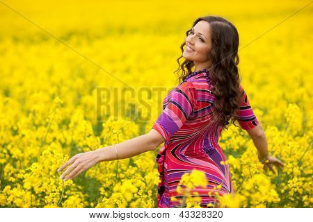 Vibrant yellow canola field and cheerful girl, spring feeling from Latvia, Baltic states